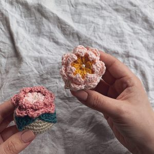 Two hands holding two blooming bauble pincushions in light pink shades over a light grey linen cloth