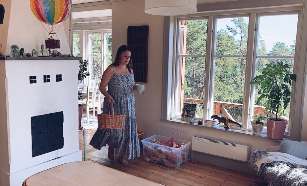 Tess carrying tea and project basked in the house