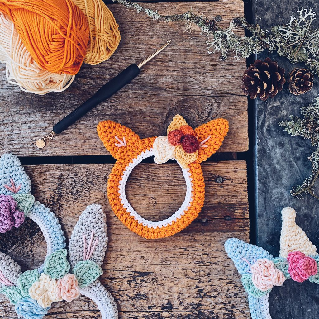 A small sized fox shaped Wallifox wallhanging is placed on a wooden backdrop together with a bunny and unicorn shaped versions, a pinecone, crochet hook and some orange and yellow coloured yarn