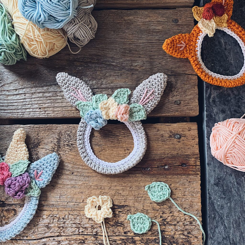 A small sized bunny shaped Wallibun wallhanging is placed on a wooden backdrop together with a fox and unicorn shaped version, small flowers and some pastel coloured yarn