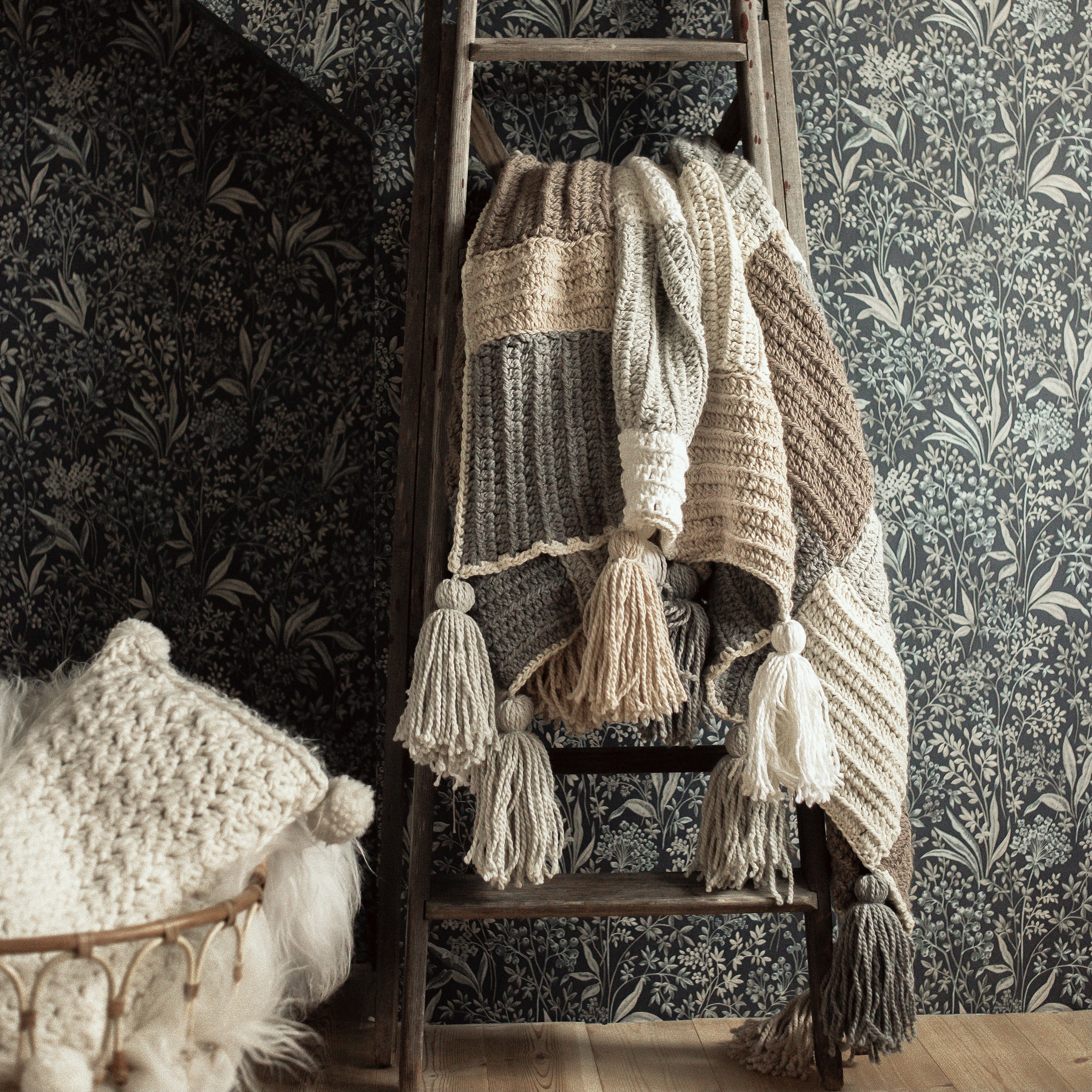 A moody pictures with the Stay Awhile Boho Blanket in soft beige and brown colors draped over a vintage latter and a cream coloured Fluffy Puffy Pillow placed in a wicker basket next to it