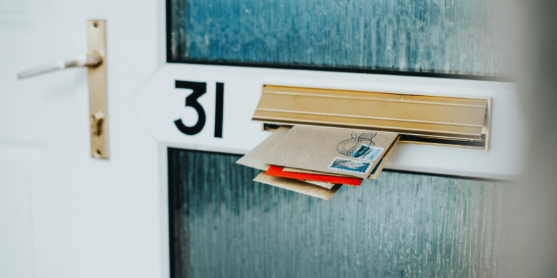 Letters in mail slot with stamps on them