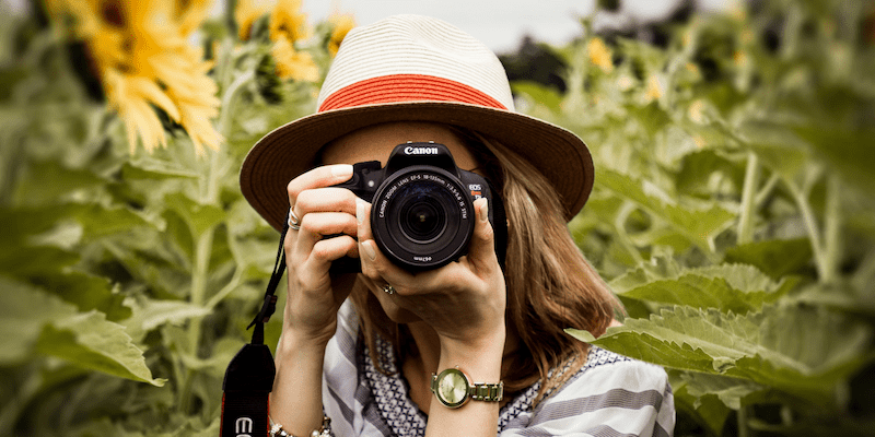 Too Zoomed In - Woman in hat with camera and sunflowers