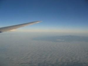 ナイロビまであと少し。ケニア・エアウェイズKQ311便から、ケニア最高峰マウント・ケニア(5199m)を臨む。アフリカではキリマンジャロ(5895m)に次ぐ2番目の高さ。雲海の間から、立派な山容を覗かせる。