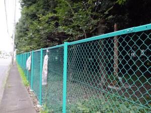 慰霊碑はフェンスの奥にあり近づくことができない。金網には千羽鶴が供えられている。(撮影=bg)