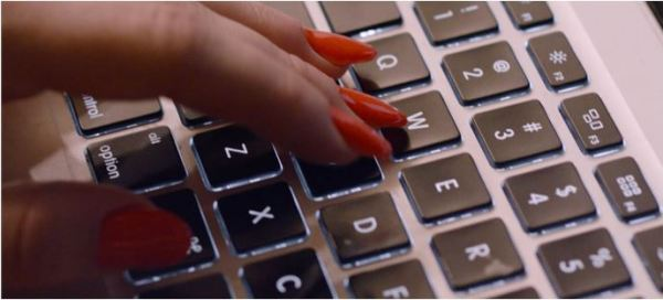 Mulher usando esmalte e digitando no computador