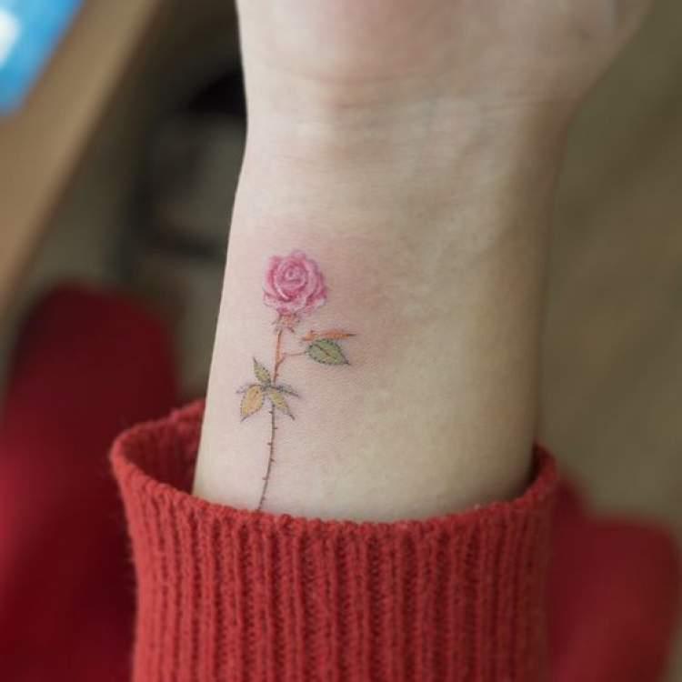 Tatuagem delicada de flor no braço