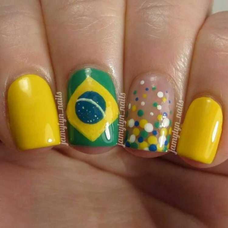 Unhas decoradas com a bandeira do Brasil e poás nas cores do Brasil