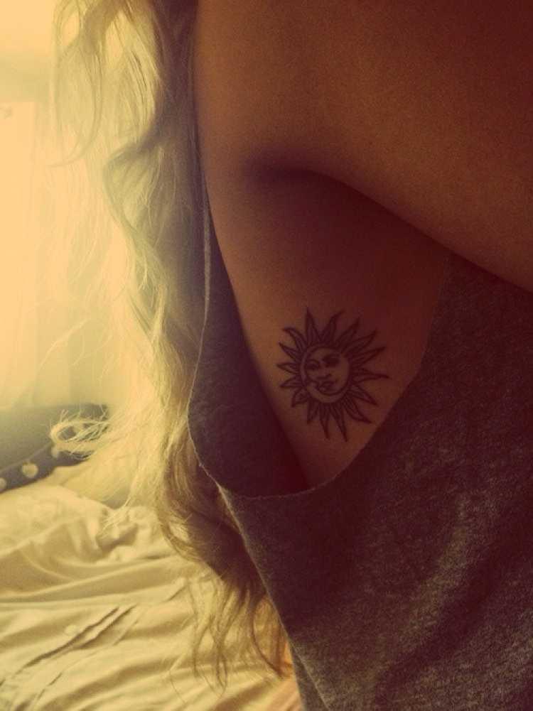 Mulher com o desenho do sol tatuado na costela embaixo do braço