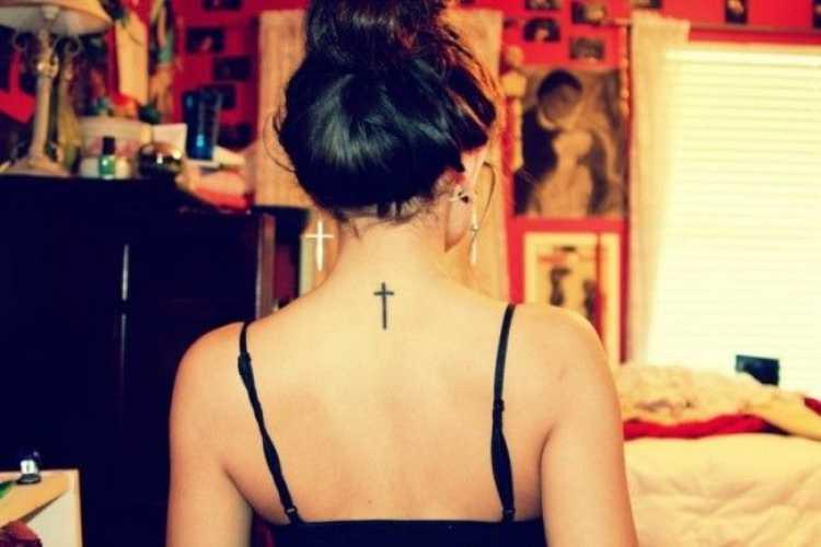 Tatuagem feminina no formato de um crucifixo na parte de trás do pescoço