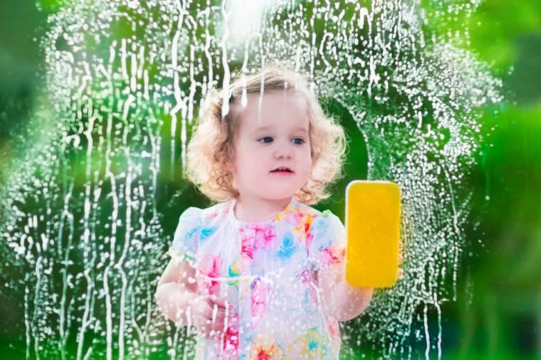 Menina limpando a vidraça com esponja