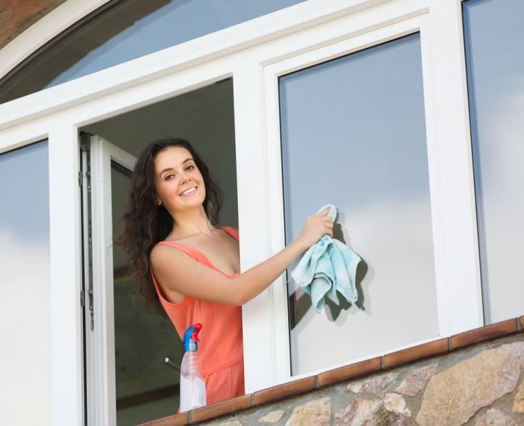 Mulher limpando a janela de vidro da casa