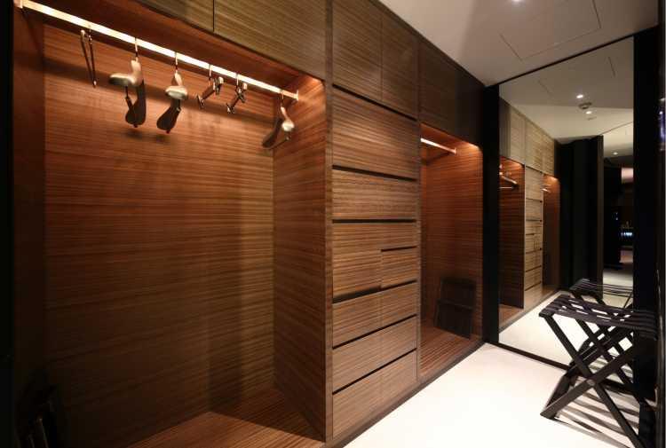 closet em madeira iluminado com araras