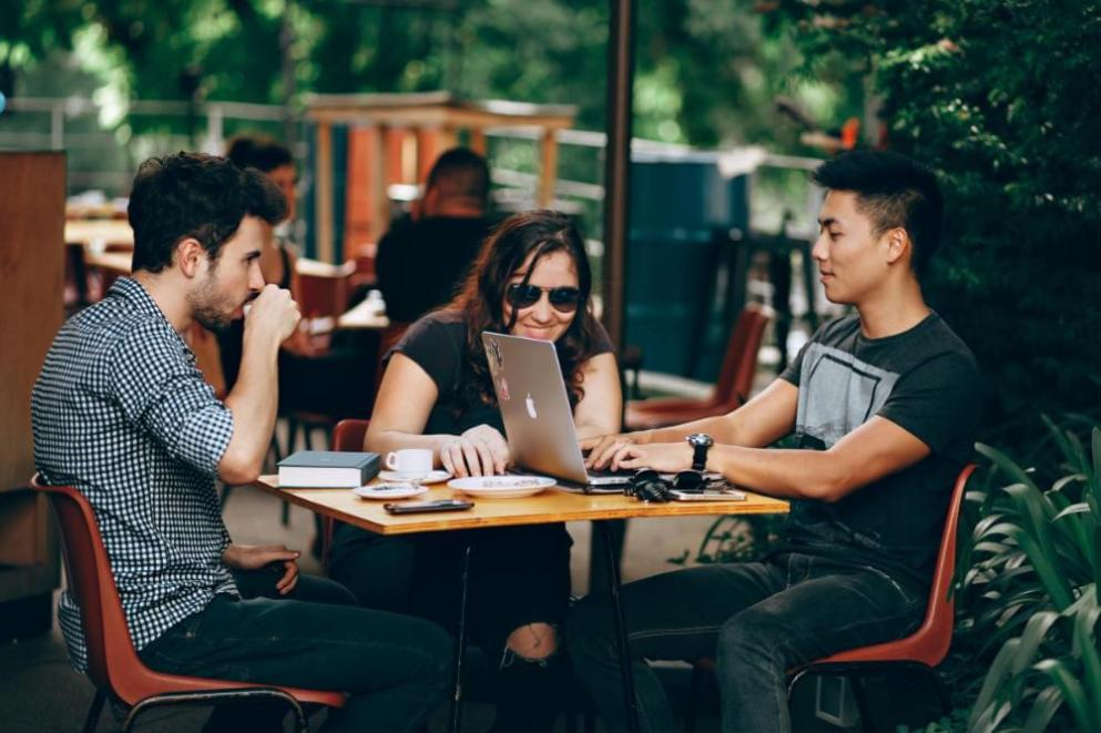 people sitting at table with laptop