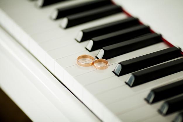 dos-hermosos-anillos-boda-teclado-piano-primer-plano_118454-834