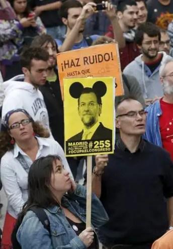 Una mujer sujeta una pancarta con la cara de Rajoy.