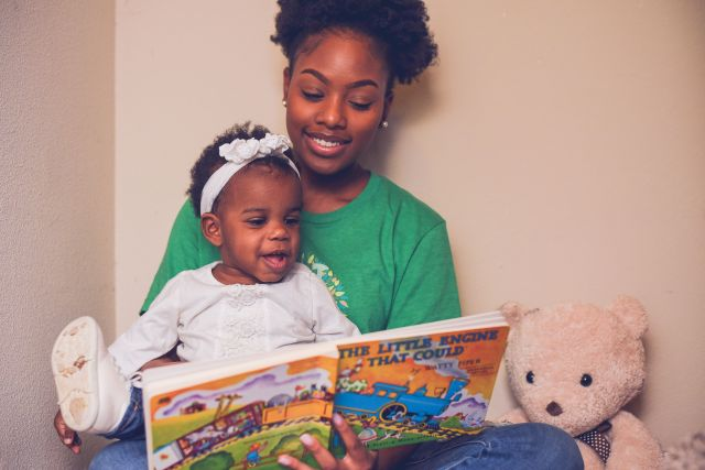 Babysitter reading book to toddler.