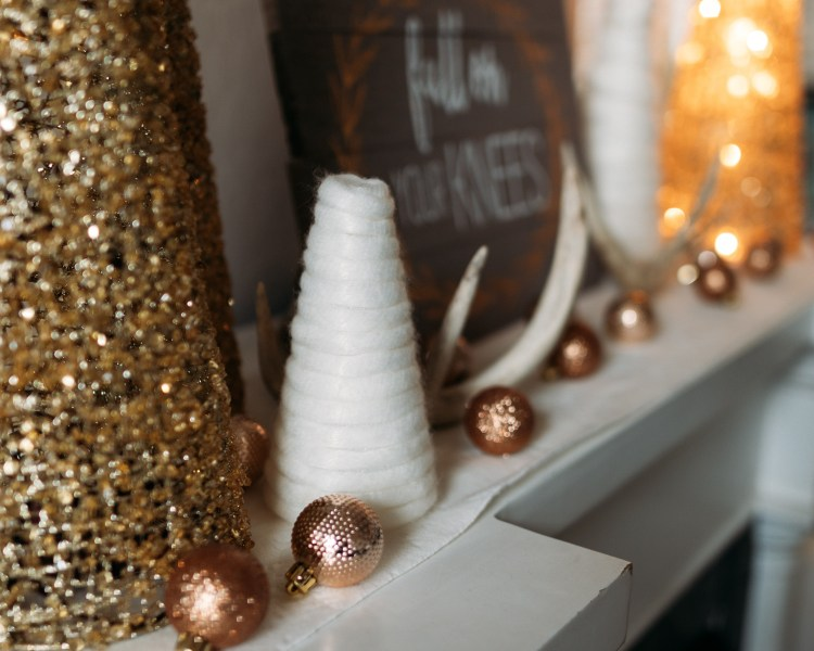 Holiday Decor | Christmas Mantle | Mantlescape | Winter Mantle | Elegant Mantlescape | Gold and White Mantle Decor | Gorgeous DIY mantle scape for winter with gold and white trees. Find the tutorial for the yarn-wrapped trees at SixCleverSisters.com.