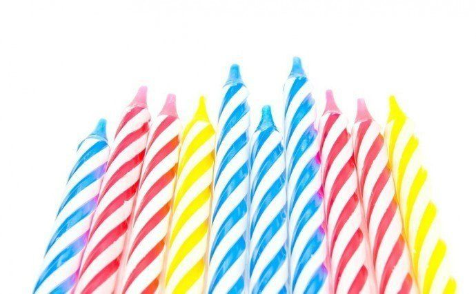 ten colorful Birthday Candles on white background closeup