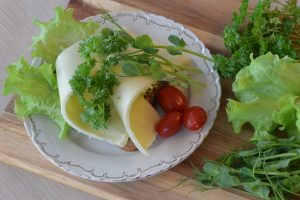 Macka på tallrik med gröna blad och tomater