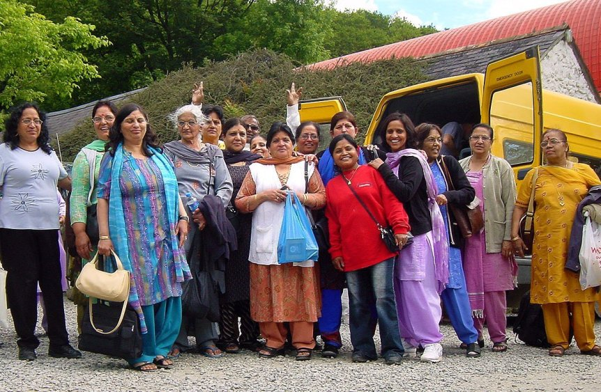 A coach group of Hindu pilgrims smile for the camera by a yellow minibus at Skanda Vale Ashram