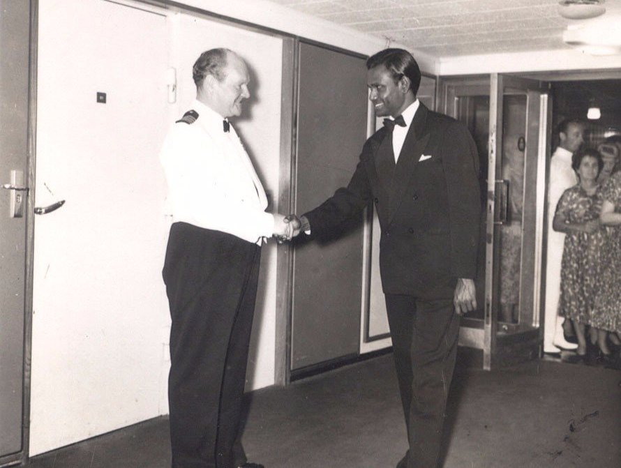 Guru Sri Subramanium in a dinner suit aboard the boat travelling from Sri Lanka to the UK. He shakes hands with the captain.
