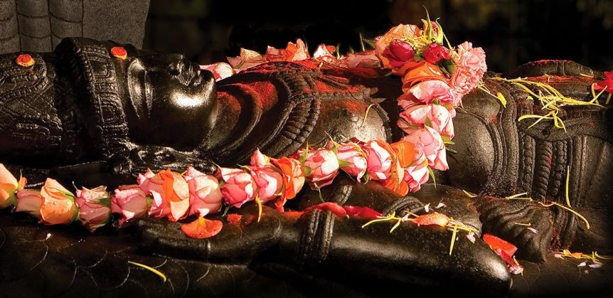 A close up of Sri Ranganatha, 'sleeping Vishnu' with a beautiful flower garland, taken at night time at Skanda Vale Ashram in the UK
