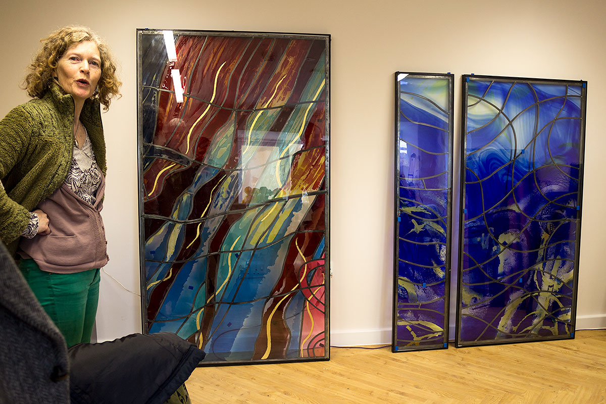 Stained glass artist Catrin Jones with two pieces of glass at Skanda Vale Hospice