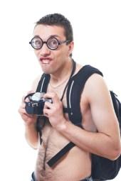 Portrait von einem jungen NErd mit dicker Brille, Fotokamera in der Hand ohne Hemd, mit vielen Haaren auf der Brust  und Rucksack auf