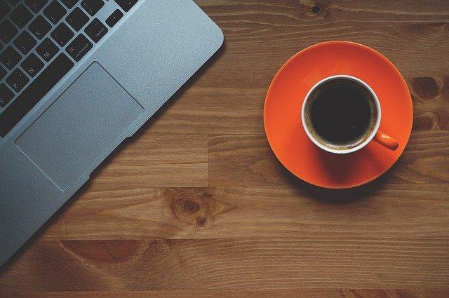 EIn kAffee auf einem Tisch neben einem Laptop
