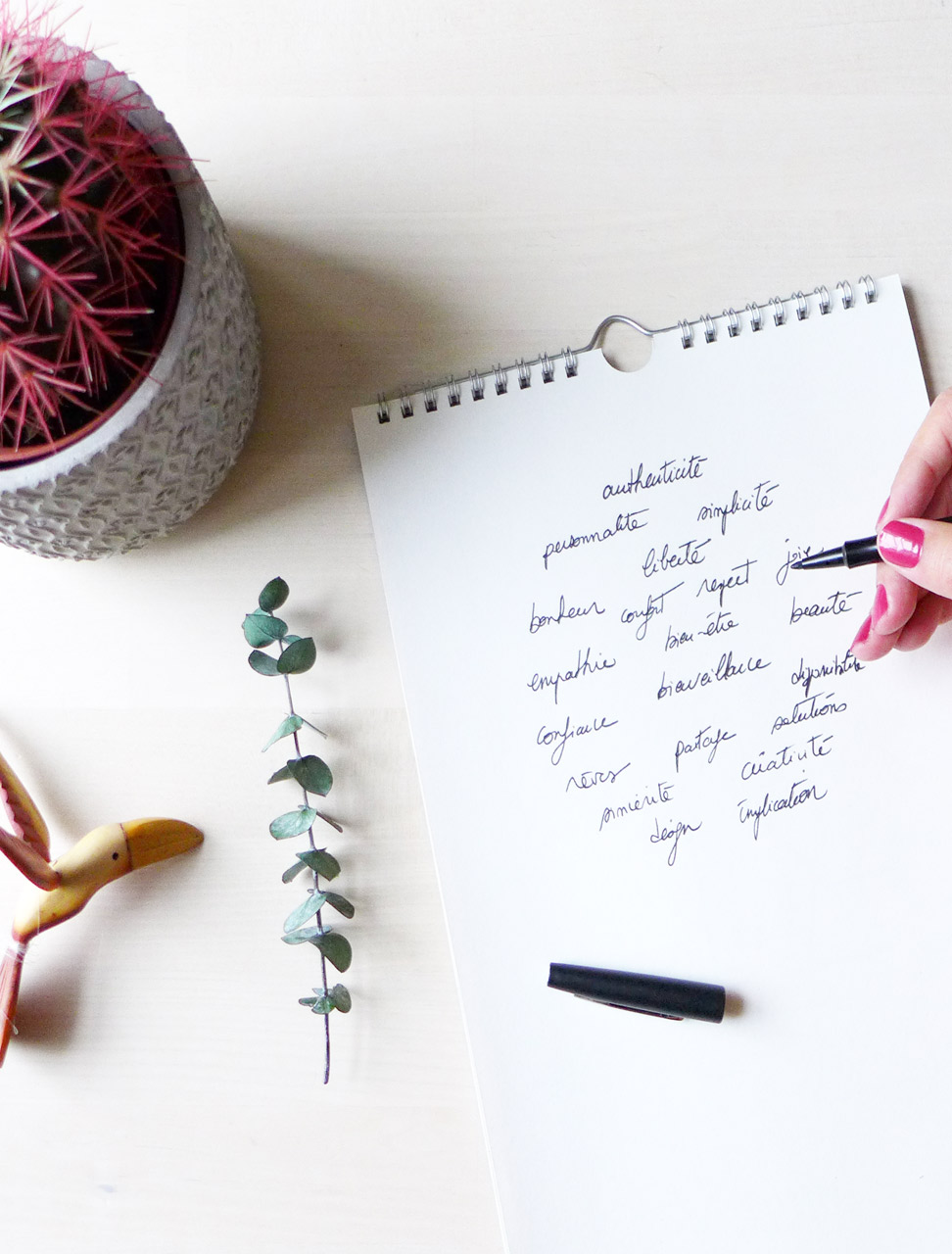 Illustration. Un bloc avec des mots clés jetés sur la papier, un cactus, une branche d'eucalyptus et une sculpture d'oiseau en bois sont disposés sur un fond bois.