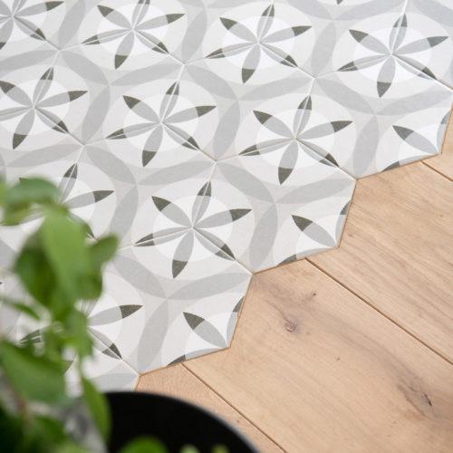 La découpe du parquet en chêne massif suit de façon originale le format hexagonal du carrelage imitant le carreaux de ciment à motif géométrique gris et blanc.