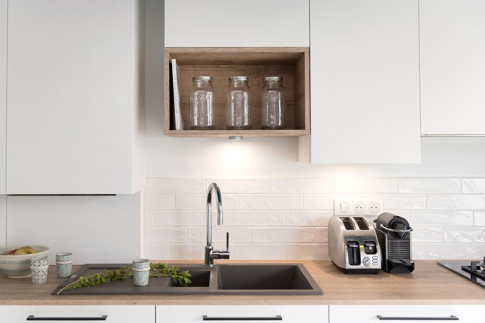 Une cuisine blanche très épurée avec un carrelage métro, un évier gris anthracite et un plan de travail en bois.