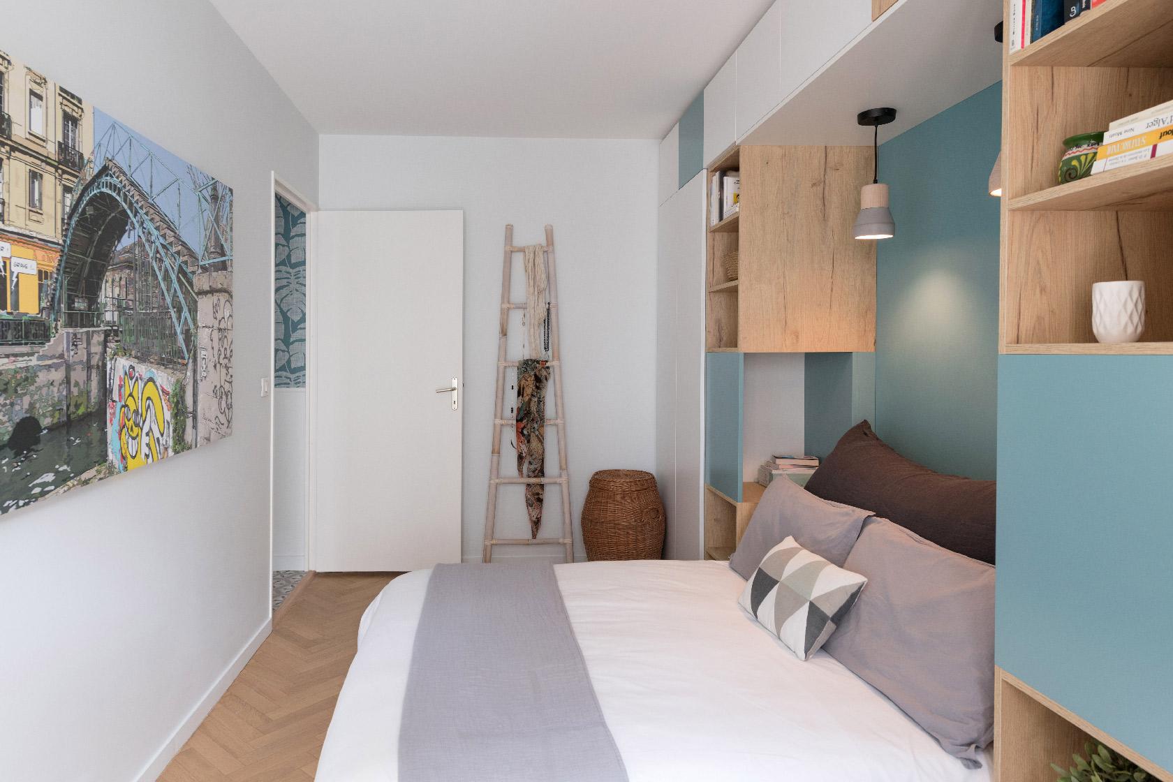 Un lit point blanc, bleu et bois accueille un un dressing, des étagères, deux chevets, deux suspensions. Le lit en 140 cm est orné de draps de lin et d'un coussin de corps gris et blanc.