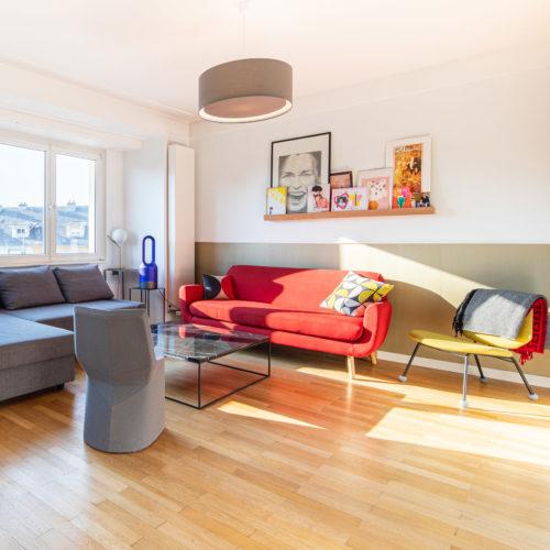 Réalisation du studio d'architecture et de décoration Skéa Designer. Inspiration Mondrian. Un salon avec canapé rouge, un canapé gris et un fauteuil jaune.