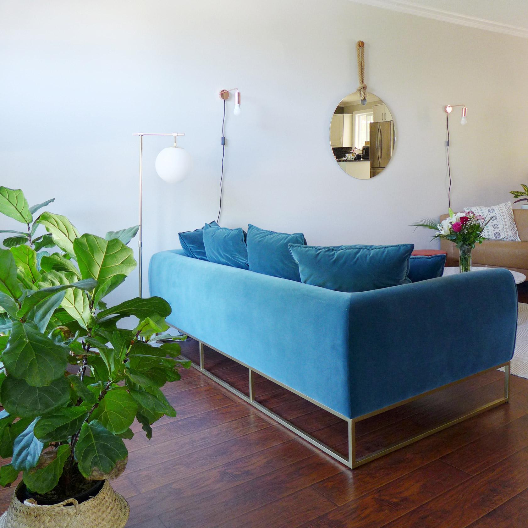 Réalisation du studio d'architecture et de décoration Skéa Designer. Velouté.Vue d'un canapé en velours bleu et de sa structure métallique dorée.