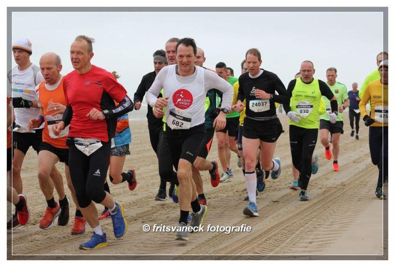 Groepje lopers op het strand bij de Egmond Halve Marathon