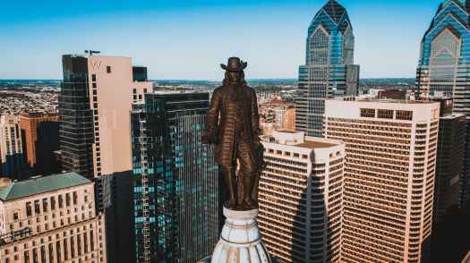 bronze statue of founder of city on top of building