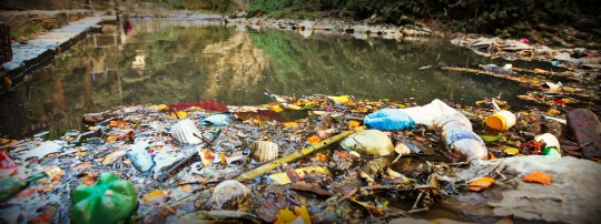 Garbage and Plastic Bottle In Polluted River