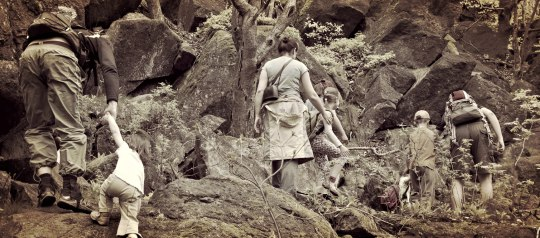 family climbing over boulders on a hike
