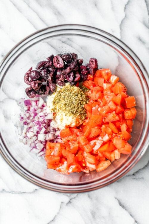 помидоры, черные оливки и красный лук в миске