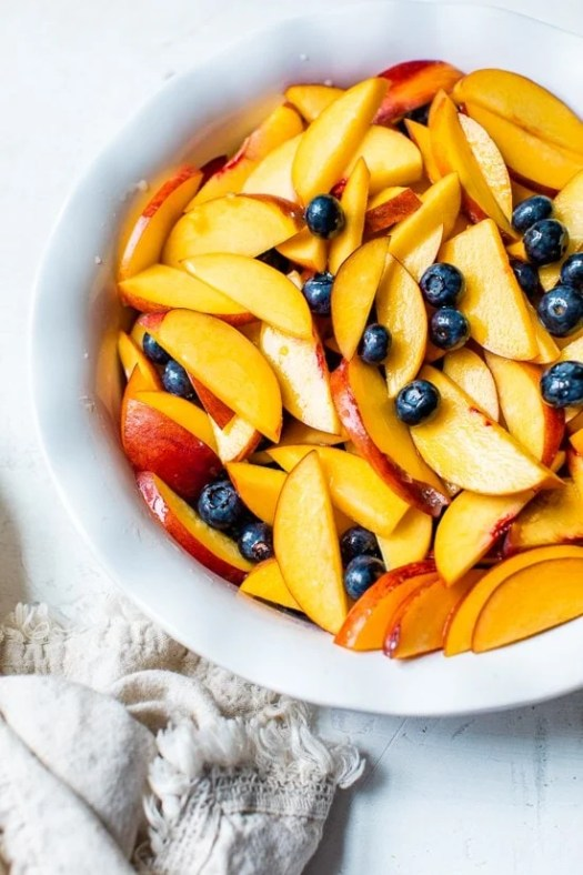 peaches and blueberries in a pie dish