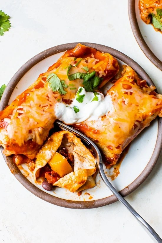 Easy vegetarianenchiladas made with butternut squash and black beans, smothered with enchilada sauce and cheese, then baked in the oven. A delicious recipe that's perfect for meatless Mondays!