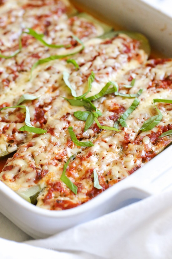Zucchini boats stuffed with a veggie lasagna filling topped with marinara sauce and cheese.