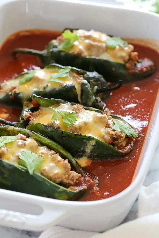 These baked Turkey Enchilada Stuffed Poblanos Rellenos are stuffed with a flavorful ground turkey filling, topped with my homemade enchilada sauce and cheese. These are so much lighter than restaurant chile rellenos which are typically battered in egg and deep fried.