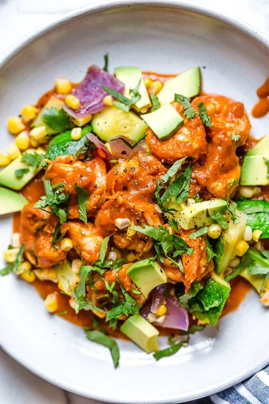 This delicious Mexican Shrimp dish is made with saucy Chipotle shrimp served over a bed of corn, zucchini, and red onions, and served with a side of avocado.
