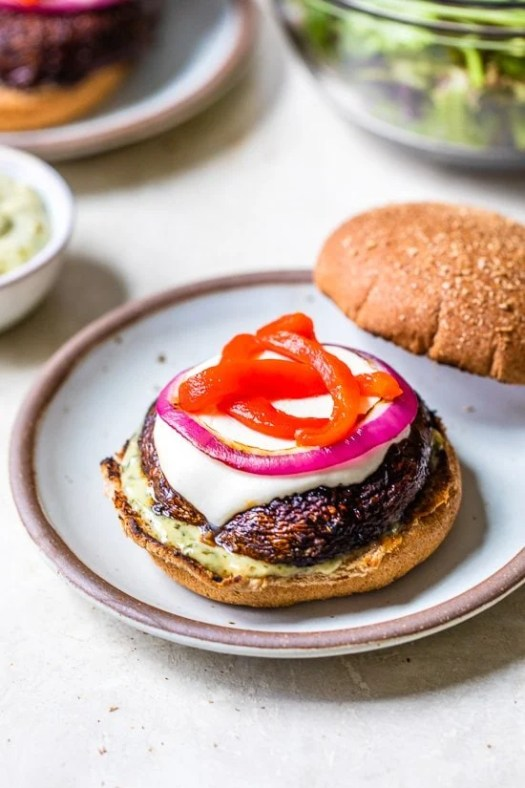 These grilled Portobello Mushroom Burgers topped with mozzarella, red peppers, and pesto mayo, are delicious and an excellent vegetarian burger option.