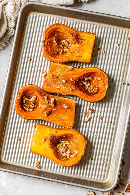 Close up of honeynut squash roasted with maple and pecans on a sheet pan.