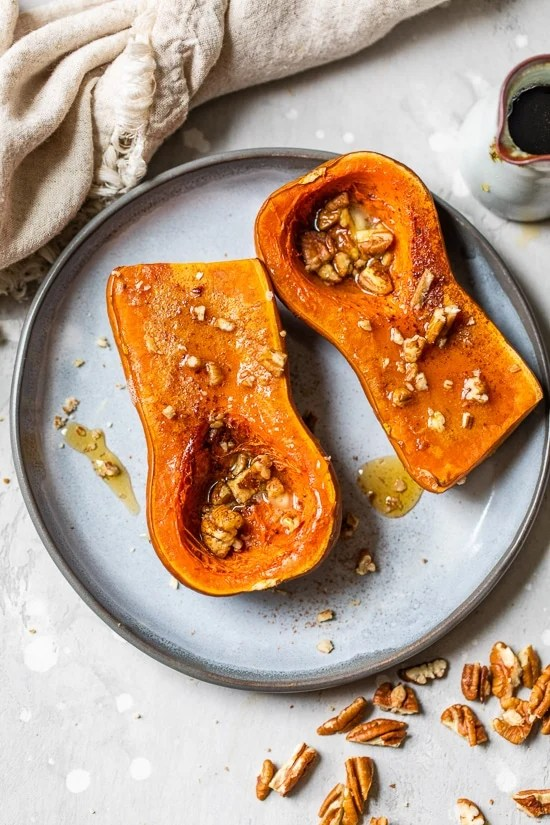 Honeynut squash on a plate with pecans.