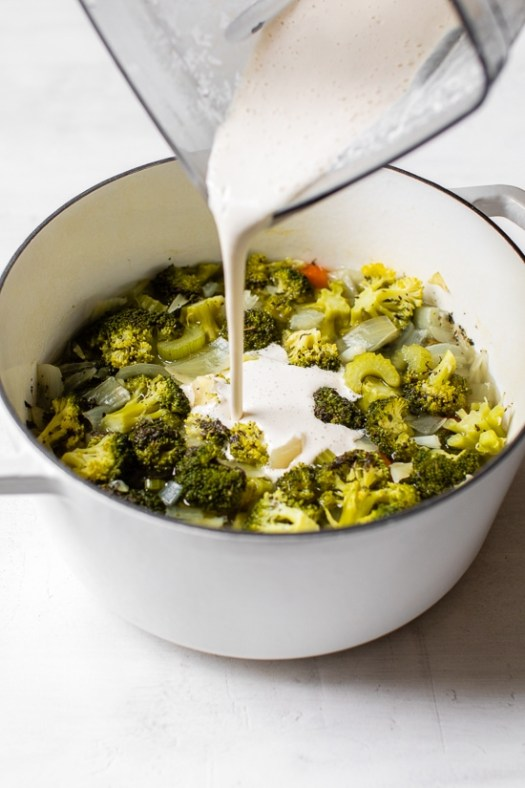 Pouring cashew milk into a pot of cooked vegetables.
